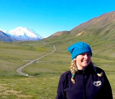 Kirsten Thompson stood in front of tundra with Mount Denali in the background in Denali National Park Alaska, USA.