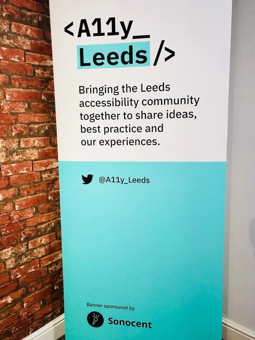 Photo of the Accessibility Leeds banner poster. With the text: < A11y_Leeds /> Bringing the Leeds accessibility community together to share ideas, best practice and our experiences. Twitter: @A11y_Leeds banner sponsored by Sonocent