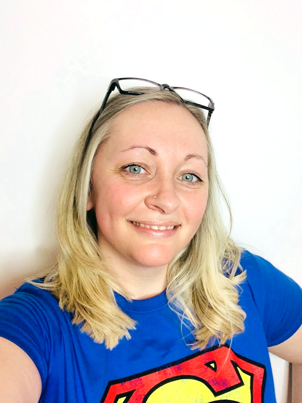 A medium close-up of Kirsten Thompson wearing a Superman t-shirt with black-framed glasses on her head.